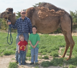 Kyle, Evan, and Asher with one of the farm's camels